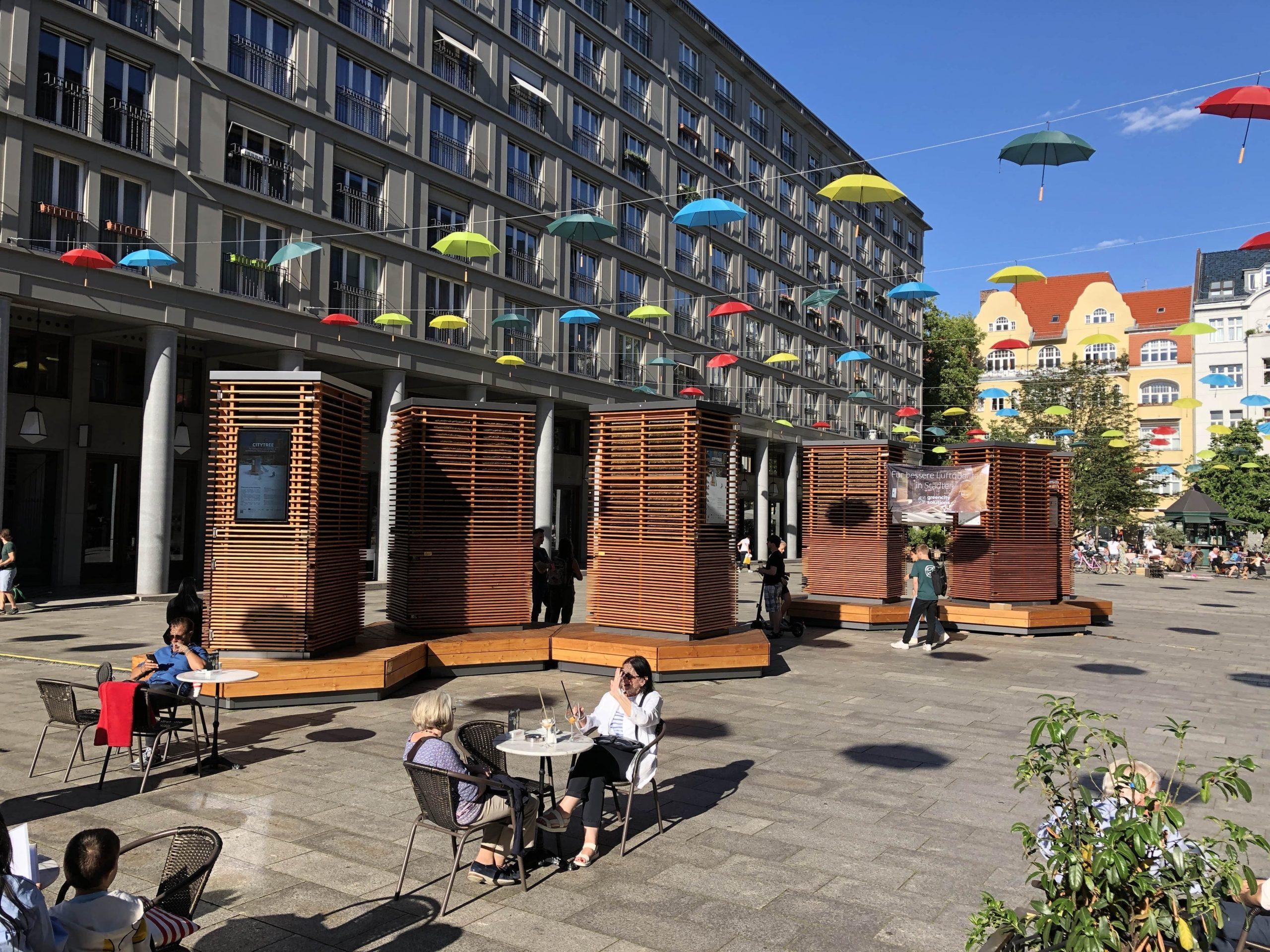 6 City Trees auf dem Walter-Benjamin-Platz bei Sonnenschein.