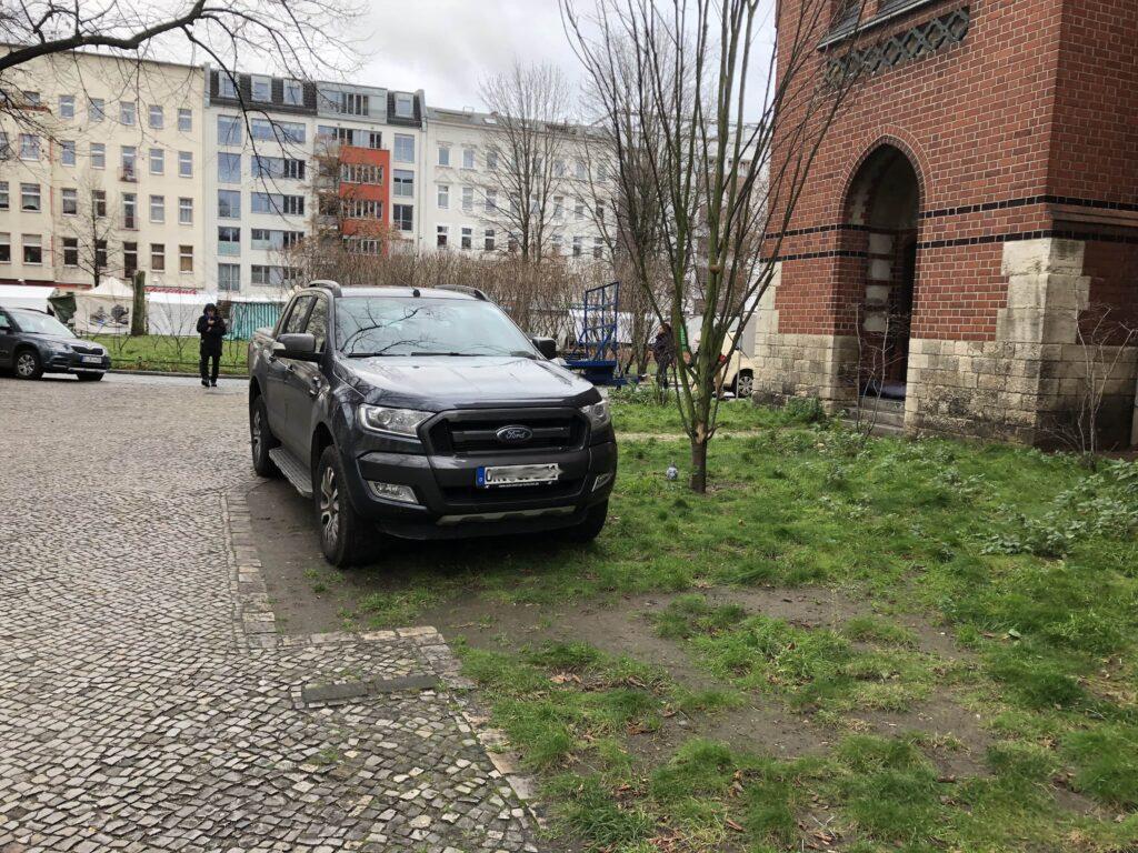 SUV steht in einer Grünanlage.