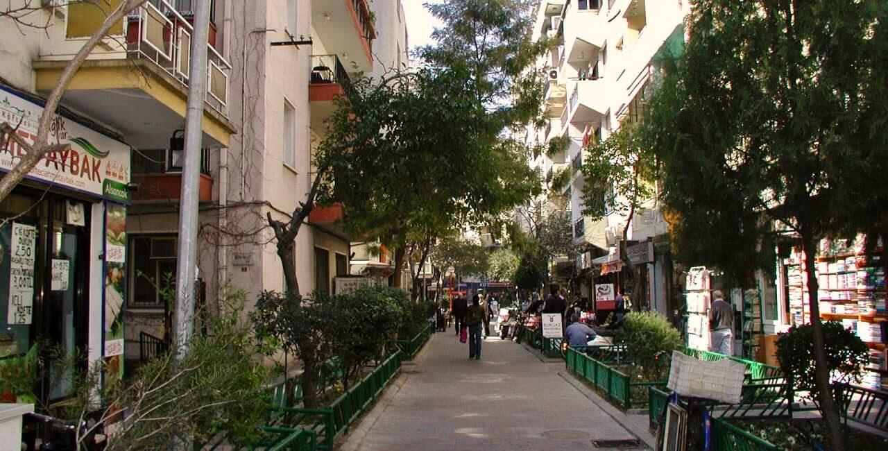 autofreie Straße mit viel Grün, Straßenleben und kleinen Läden.
