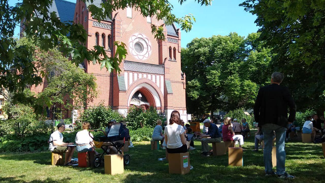 Menschen aus dem Karl-August-Kiez sitzen auf Papphockern vor der Trinitatis-Kirche.